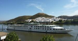 El crucero fluvial La Belle de Cadix junto a un pueblo típico del bajo Guadiana.